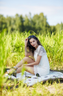 Young blonde woman in white dress and sunglasses is sitting on a blanket in tall grass.