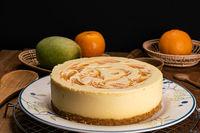 Side view of homemade mango cheesecake in ceramic dish.