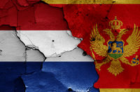 flags of Netherlands and Montenegro painted on cracked wall