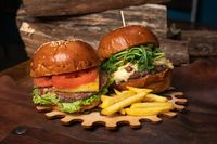 Tasty craft fresh beef burgers with french fries, one with fried walnuts are served on a decorative wooden part of a simple mechanism. Fast food restaurant concept. Street food concept