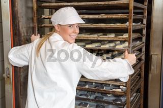Bäckerin schiebt Regal voller Teiglinge in Backofen