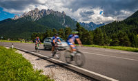Cyclists riding a bicycle on the road in the background the Dolomites Alps Italy.