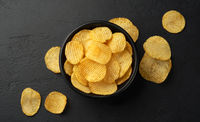 Ridged potato chips in bowl on black background, top view