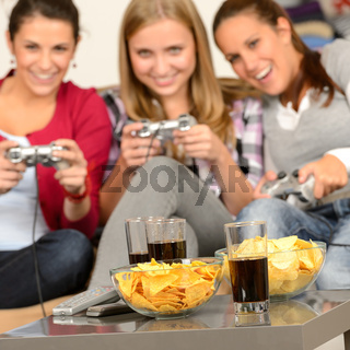 Smiling teenage girls playing with video games