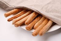 Fresh baked Italian grissini breadsticks covered with cloth