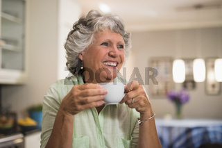 Happy senior woman holding cup at home