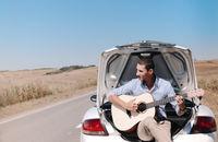 Happy young man enjoying road trip