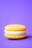yellow Cake macaron or macaroon on purple background.