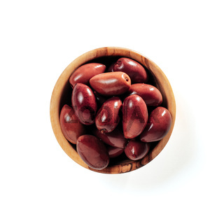 red kalamata olives in wood bowl isolated on white