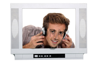 man with headphones behind TV