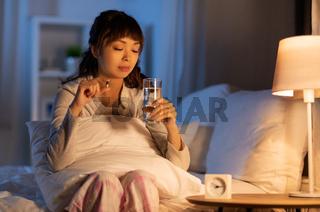 stressed asian woman taking medicine at night