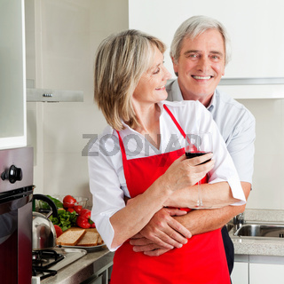 Senior umarmt Frau in Küche