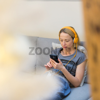 Young thoughtful woman sitting indoors at home living room sofa using social media on phone for video chatting and staying connected with her loved ones. Stay at home, social distancing lifestyle