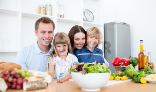 Smiling parents and their children preparing dinner together