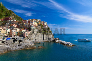 Village of Manarola with ferry, Cinque Terre, Italy