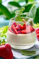 Panna cotta with coconut cream, matcha tea and ripe strawberries.