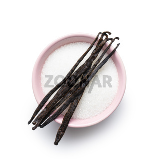 Vanilla pods and sugar in bowl. Sticks of vanilla