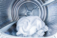 Inside of tumble dryer with clean white towels - new generation of dryer