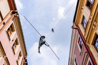 sculpture of a trapeze artist in a narrow street in the historic city center of Lublin
