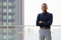 Portrait of handsome African businessman outdoors at rooftop with arms crossed