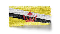 Brunei flag on a piece of cloth on a white background