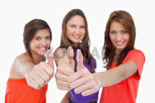 Smiling teenagers showing their approval by putting their thumbs up