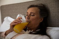 Senior woman drinking juice in bed at home
