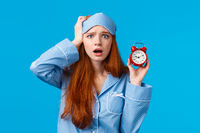 Anxious, panicking young redhead girl missed interview, overslept, holding red alarm clock and touching head frustrated with concerned face, wearing nightwear and sleep mask, blue background