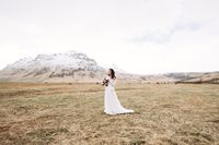 Portrait of a bride in a white wedding dress, with a bride's bouquet in her hands. In a field of dry yellow grass, amid a snowy mountain and grazing Icelandic horses. Destination Iceland wedding.