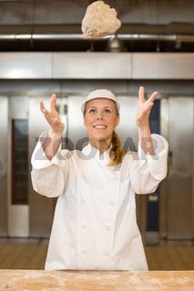 Bäckerin wirft Teig für Brot in einer Bäckerei in die Luft