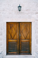 Wooden brown doors with carved elements and patterns in a white wall with a lantern.
