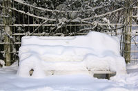 A deep snowy bench in a park
