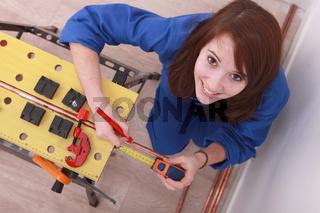 Woman measuring copper pipe