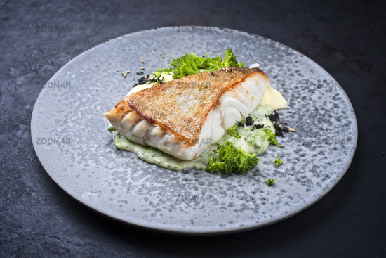 Modern style traditional fried skrei cod fish filet with mashed potatoes and baby broccoli served as close-up on ceramic design plate with copy space