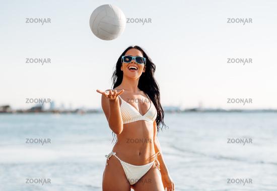 woman in bikini playing with volleyball on beach