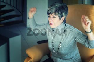 Frau sitzt jubelnd vor einem Fernsehgrät