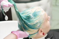 Washing green hair color of young woman with shampoo in hair salon