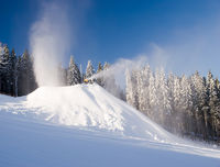 snow guns and makers in action in winter on the snowy hill with forest in background