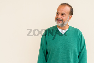 Portrait of handsome bearded Indian man against plain wall
