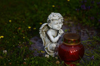 White marble grave angel sitting in front of red g