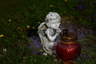 Weißer Marmorengel sitzt vor rtem Grablicht