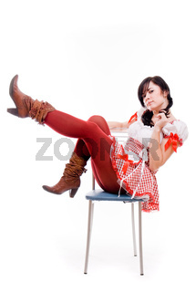 Sexy woman in a red dress sitting on a chair on white background