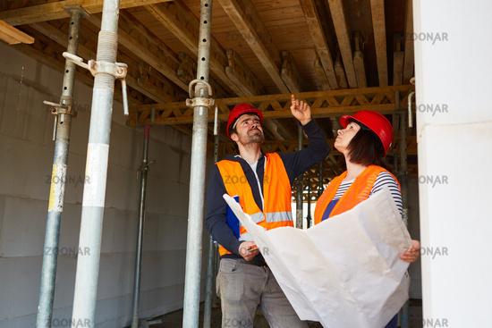 Polier und Architektin diskutieren Sanierung einer Decke