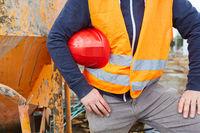 Arbeiter trägt roten Schutzhelm unter dem Arm auf Baustelle