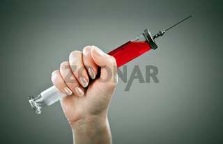 Old medical syringe on a grey background