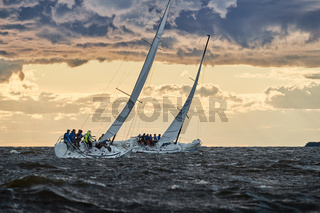 Russia, St. Petersburg, 23 July 2021: Competition of two sailboats on the horizon in sea at sunset, the amazing storm sky of different colors, race, big waves, sail regatta, cloudy weather, sun beams