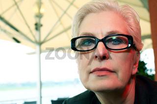 weißhaarige Frau über 50 mit Brille