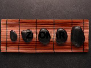 Five massage stones on a bamboo mat