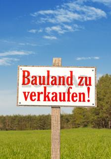Schild auf der grünen Wiese: Bauland zu verkaufen! Hochformat
