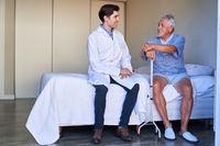 Krankenpfleger und Senior sitzen auf dem Bett und reden
